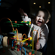 A ten month old baby girl playing with a wooden play station and abacus. Photo Tim Clayton