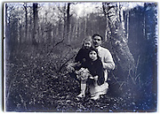 father with two children posing in the woods vintage 1900s