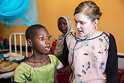 Dr Siobhan Neville examines 10 year old Leyla Msamu who has malaria on the children's ward during the daily rounds.  The rounds are attended by all the medical staff who work on that ward, doctors, nurses and attendants.  St Walburg's Hospital, Nyangao. Lindi Region, Tanzania.