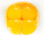 four raw egg yolks in a bowl