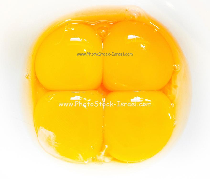four raw egg yolks in a bowl