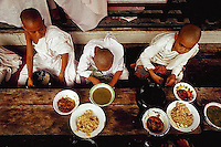 September 1987, Mandalay, Burma (Myanmar) --- Monks eat lunch at a monastery in Mandalay, Burma. --- Image by © Owen Franken/CORBIS