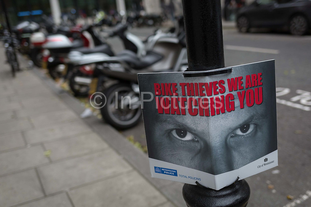 A pair of eyes warn ever-present bike and scooter thieves that theyre being watched by the Met Police, on 22nd November 2017, in London England.