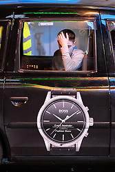 """© Licensed to London News Pictures . 24/12/2016 . Manchester , UK . A man leans out of a taxi window for fresh air after being carried to the cab by a friend . Revellers out in Manchester City Centre overnight during 2016's second """" Mad Friday """" , named for historically being one of the busiest nights of the year for the emergency services in the UK . Photo credit : Joel Goodman/LNP"""