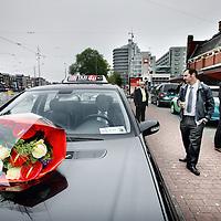 Nederland, Amsterdam , 1 juni 2013.<br /> Presentatie nieuwe taxiregels bij Centraal station voor taxichauffeurs in Amsterdam.<br /> Vanaf a.s. zaterdag worden de nieuwe taxiregels in Amsterdam gehandhaafd. Die komen erop neer dat elke chauffeur moet zijn aangesloten bij een taxionderneming-met-vergunning. Het aantal toegelaten chauffeurs daalt daardoor van zo'n 4000 tot 2300, en het is uiteraard de bedoeling dat zo vooral de slechtsten geweerd worden.<br /> Het handhaven start officieel om acht uur 's ochtends bij het Centraal Station - waar, samen met het Leidseplein, de chaos altijd het grootst is. Daar zullen alle betrokkenen (onder meer de burgemeester en taxidirecteuren) aanwezig zijn.<br /> Opvallend was de aanwezigheid van het milieu bewuste taxi bedrijf Taxi-electric die mooie jonge dames met groene ballonnen liet rondlopen tijdens de presentatie op het Centraal Station.<br /> Foto:Jean-Pierre Jans