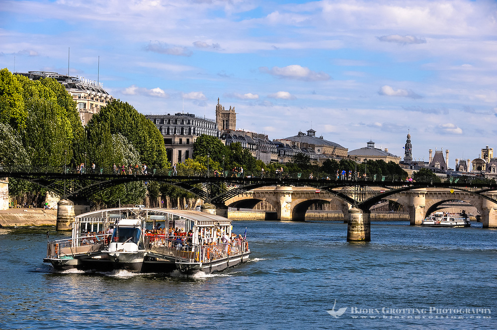 Paris, France. View from a boat on the river Seine. View east with Saint-Jacques Tower in the background. The Pont des Arts  is a pedestrian bridge. Pont Neuf in the background.