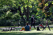 The girl who revealed her breast and raised two fingers (V for victory or freedom) is seen sunbathing with a friend along London's Hyde Park on Friday, May 15, 2020. (Photo/ Vudi Xhymshiti)