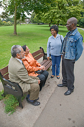 Two couples greeting each other in the park,
