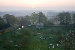 View over the orchard to countryside beyond from the Tower at Sissinghurst Castle Garden at dawn