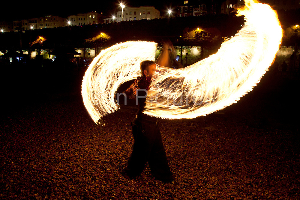 """Brighton, UK. Friday 21st December 2012. Fire show on the beach. Burning the Clocks has been a Brighton tradition for almost two decades. This event takes place on the winter solstice, the shortest day of the year. A 2,000-strong parade winds its way through the streets and people pass their handmade paper and willow lanterns – filled symbolically with their hopes and dreams – into a blazing bonfire to """"burn the clocks"""" and welcome in the new longer day."""