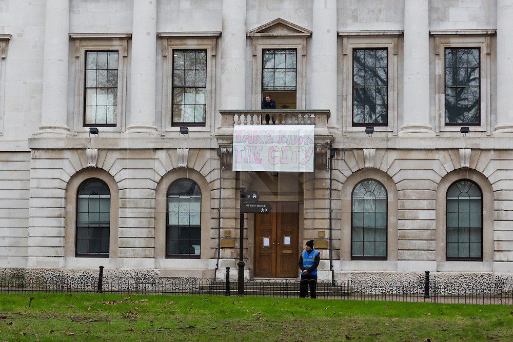 """© Licensed to London News Pictures. 30/12/2015. London, UK. A squatter sits on the balcony of the Royal Mint building with a banner saying """"Take back the city"""" whilst a security man stands outside. Squatters have occupied the former Royal Mint building, located opposite the Tower of London on the border of the City of London to protest against homelessness and highlight how empty buildings could provide shelter for rough sleepers. The site was previously used to manufacture British coins but is currently vacant and activists argue that this along with other vacant commercial buildings could be used to provide short term shelter for the homeless. Photo credit : Vickie Flores/LNP"""