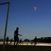 A Hang glider prepares to land on the beach in the late afternoon light at Sao Conrado beach as locals play football on the beach, Rio de Janeiro,  Brazil. 8th July 2010. Photo Tim Clayton..The beaches of Rio de Janeiro, provide the ultimate playground for locals and tourists alike. Beach activity is in abundance as beach volley ball, football and a hybrid of the two, foot volley, are played day and night along the length and breadth of Rio's beaches. .Volleyball nets and football posts stretch along the cities coastline and are a hive of activity particularly at it's most famous beaches Copacabana and Ipanema. .The warm waters of the Atlantic Ocean provide the ideal conditions for a variety of water sports. Walkways along the edge of the beaches along with exercise stations and cycleways encourage sporting activity, even an outdoor gym is available at the Parque Do Arpoador overlooking the ocean. .On Sunday's the main roads along the beaches of Copacabana, Leblon and Ipanema are closed to traffic bringing out thousands of people of all ages to walk, run, jog, ride, skateboard and cycle more than 10 km of beachside roadway. .This sports mad city is about to become a worldwide sporting focus as they play host to the world's biggest sporting events with Brazil hosting the next Fifa World Cup in 2014 and Rio de Janeiro hosting the Olympic Games in 2016...
