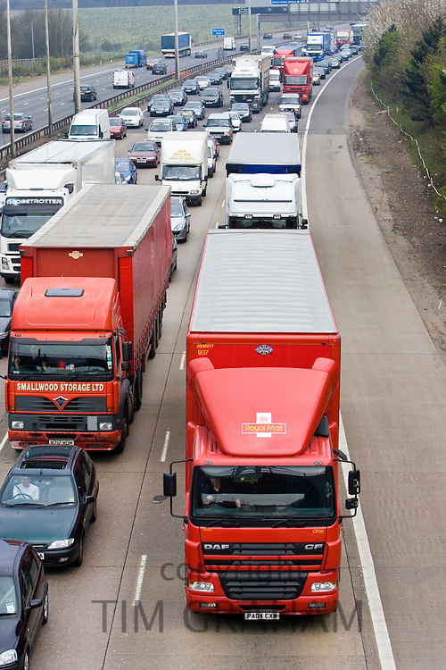 Royal Mail lorry travelling slowly among heavily congested traffic on M1 motorway in Hertfordshire, United Kingdom