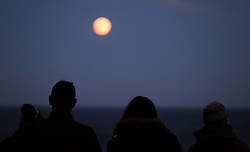 © Licensed to London News Pictures. 24/12/15<br /> Saltburn-by-the-Sea, UK. A group of friends stop and look as the moon rises over cliffs at Saltburn by the Sea on Christmas Eve. A full moon will appear in the skies over Britain on Christmas day, for the first time in decades. The last time there was a full moon on 25 December was 1977, and the next one won't be until 2034.The full moon, which is the last of the year, is called the Full Cold Moon because it occurs at the start of winter. Photo credit : Ian Forsyth/LNP