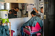 A barber cuts a client's hair in a traditional salon in the backstreets of Antigua, Guatemala.