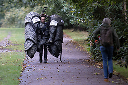 © Licensed to London News Pictures. 03/10/2021. London, UK. A charity worker from Save The Rhino carries rhino costumes in Greenwich Park ahead of the start of the London Marathon.This London Marathon will be the first full scale staging of the race in more than two years due to the Coronavirus Pandemic.  Photo credit: George Cracknell Wright/LNP