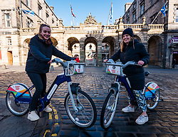 City Chambers, Edinburgh, Scotland, United Kingdom, Just Eat E-bikes: A new fleet of 163 rentable e-bikes are launched and integrated into the capital's existing cycle hire scheme by Just Eat Cycles. Edinburgh will now have the largest docked e-bike fleet in UK. Pictured: Just Eat bike staff Charlotte & Greta with the new bikes.<br /> Sally Anderson | EdinburghElitemedia.co.uk