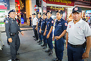 "26 SEPTEMBER 2014 - PATTAYA, CHONBURI, THAILAND: Tourist police start their shift on Walking Street in Pataya. Pataya, a beach resort about two hours from Bangkok, has wrestled with a reputation of having a high crime rate and being a haven for sex tourism. After the coup in May, the military government cracked down on other Thai beach resorts, notably Phuket and Hua Hin, putting military officers in charge of law enforcement and cleaning up unlicensed businesses that encroached on beaches. Pattaya city officials have launched their own crackdown and clean up in order to prevent a military crackdown. City officials have vowed to remake Pattaya as a ""family friendly"" destination. City police and tourist police now patrol ""Walking Street,"" Pattaya's notorious red light district, and officials are cracking down on unlicensed businesses on the beach.     PHOTO BY JACK KURTZ"