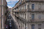Aerial view of apartments, parked cars and a single pedestrian on Rue Baudin in Montpellier, south of France.