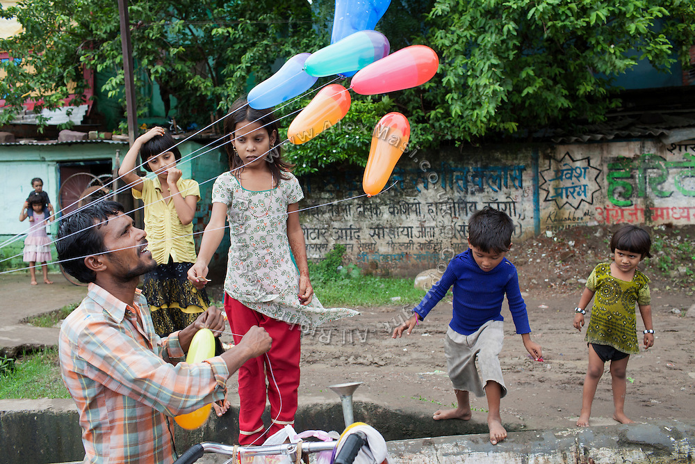 A girl, followed by younger children, is buying a balloon from a local vendor passing near the impoverished Oriya Basti Colony in Bhopal, Madhya Pradesh, near the abandoned Union Carbide (now DOW Chemical) industrial complex.