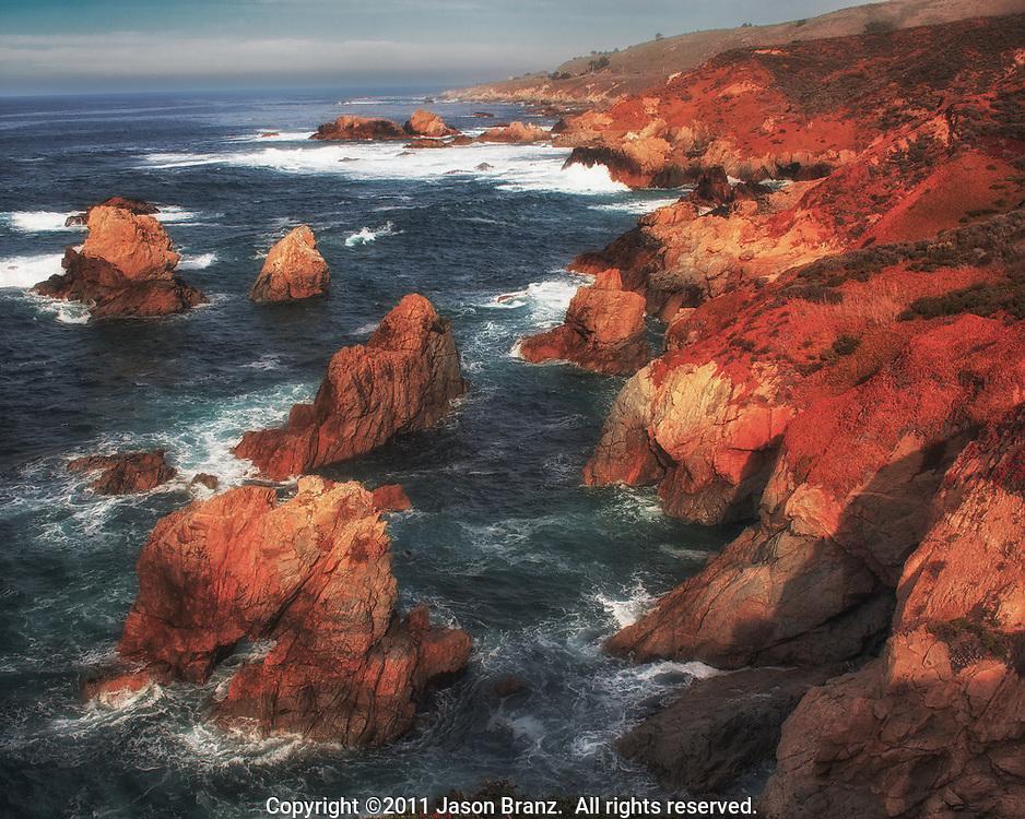 Sunrise along a rugged coastline, sea stacks, and waves, Big Sur Coast, California.