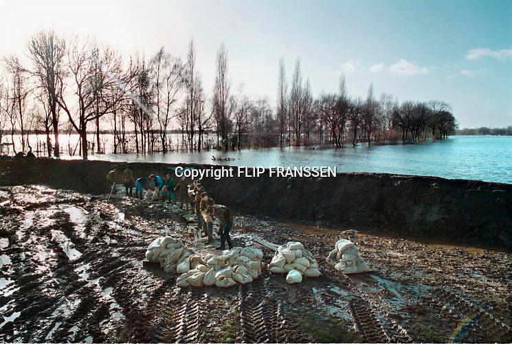 Nederland, Milsbeek, 01-02-1995Eind januari, begin februari 1995 steeg het water van de Rijn, Maas en Waal tot record hoogte van 16,64 m. bij Lobith. Een evacuatie van 250.000 mensen was noodzakelijk vanwege het gevaar voor dijkdoorbraak en overstroming. op verschillende zwakke punten werd geprobeerd de dijken te versterken met zandzakken. Hier aan de Maas bij Milsbeek bij Nijmegen.Late January, early February 1995 increased the water of the Rhine, Maas and Waal to a record high of 16.64 meters at Lobith. An evacuation of 250,000 people was needed because of flood risk. At several points people tried to reinforce the dikes with sandbags. Foto: Flip Franssen/Hollandse Hoogte