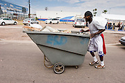 """07 AUGUST 2005 - PHOENIX, AZ: ALAN, who said he has lived on the streets of Phoenix for more than 10 years, pushes his dumpster past the Agape Harvest Church tents used for Sunday services. Alan said he collects garbage left on the street as a part of his """"atonement"""" for past sins. The mile between the Phoenix police department headquarters and the Arizona State Capitol is also Phoenix's """"Skid Row"""" where most of the homeless live and most of the homeless shelters and charity kitchens are located. Members of Agape Harvest Church come down to area on Sunday mornings and hold church services for the people in the area.  PHOTO BY JACK KURTZ"""