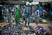 A street vendor, center, sells sandals in a busy market area in Bangui. Although the biggest import partner of CAR is Netherlands according to the CIA Factbook, most commodities are imported from Cameroon via Nigeria or China.