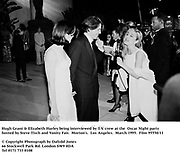 Hugh Grant & Elizabeth Hurley being interviewed by T.V. crew at the  Oscar Night party hosted by Steve Tisch and Vanity Fair. Morton's. Los Angeles. March 1995. 95550/11<br />