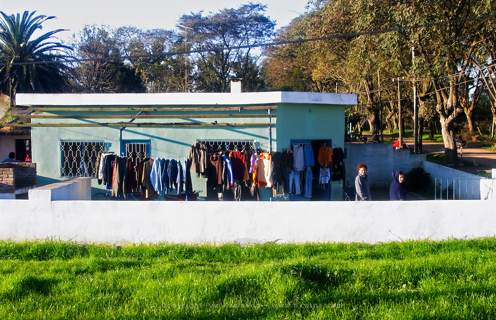 A road-side shop in Juanico selling clothes. Clothes on display outside the house hanging on hangers on metal bars. The shop keeper looking at the camera. Uruguay, South America