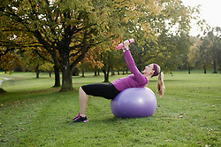 Woman in park with fitness ball and dumbbells, Woerthsee, Bavaria, Germany