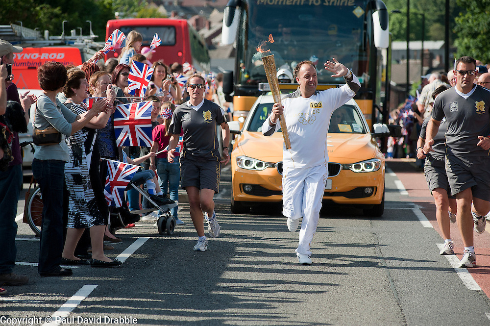 The Olympic Torch relay reaches Sheffield on day 38 coverage from the Chapeltown - Ecclesfield - Parson Cross section of the Journey.<br /> Bearer 103 Christopher Godwin carries the torch out of Chapeltown and on up Ecclesfield Road<br /> 25 June 2012.Image © Paul David Drabble