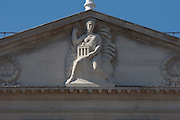 High on the top pediment is the Lady of the Bank of England with a cascade of coins by her right leg on the exterior of the Bank of England in the City of London. To her left and right are reliefs of oak leaves. She is clothed and seated on a globe. Her hair forms a stylised crown for her head. With her raised right hand she holds her cloak which billows out to her left. With her left hand she supports on her opposite knee a temple-like building, with four columns and a pediment. Beside her right leg is a cascade of coins.