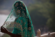 A young bride is taking a moment inside the Taj Mahal complex overlooking the heavily polluted Yamuna River, in Agra.