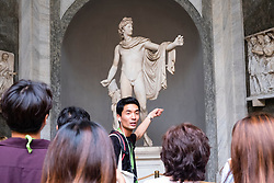 Tourist tour group looking at Apollo of the Belvedere sculpture in the Octagonal Courtyard in the Vatican Museum Rome Italy