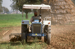 Man driving tractor on farm; harrowing the land,