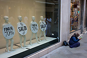 Retail mannequins advertising a 70% sale with a woman street beggar in the San Marco shopping district of Venice, Italy. The four little people normally modelling clothing are today draped with discs telling buyers of the shop's discounts. On the pavement is an unfortunate old woman who sits on the street with a cup held for Euros and cents.
