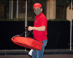 © Licensed to London News Pictures. 26/02/2021. London, UK. A pizza delivery arrives as the first travellers leave the Radisson hotel near Heathrow Airport after their quarantine period ended. New quarantine measures were introduced for travellers form red list countries, who are required to isolate for ten days in a hotel at a cost of £1,750 per person. Photo credit: Ben Cawthra/LNP