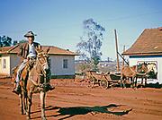 Man on horseback riding through street at Laranjeiras do Sol, Paraná state, Brazil in 1962