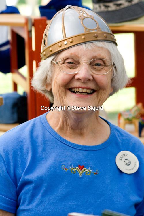 Clerk modeling replica warrior helmet of Sweden. Svenskarnas Dag Swedish Heritage Day Minnehaha Park Minneapolis Minnesota USA