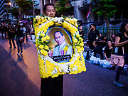 13 OCTOBER - BANGKOK, THAILAND: A man carries a portrait of the late King on the first anniversary of the death of Bhumibol Adulyadej, the Late King of Thailand. About 199 monks from 14 Buddhist temples in Bangkok participated in the mass merit making at Siriraj Hospital to mark the anniversary of the revered King's death. He will be cremated on 26 October 2017.  PHOTO BY JACK KURTZ