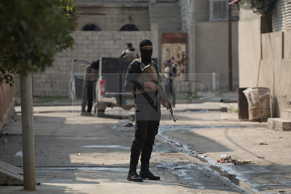 Licensed to London News Pictures. 13/02/2017. Mosul, Iraq. A masked officer of Iraq's National Security Service keeps watch as colleagues diffuse the booby trapped former home of an ISIS fighter and his family. The fighter and his family, originally from Tikrit, fled the city during the Mosul offensive leaving behind a home with two victim operated explosive devices kill anyone who tried to enter.<br /> <br /> The Jihaz Al-Amin Al-Watani, roughly translated as the National Security Service or NSS, are a secretive Iraqi agency that works under the responsibility of the Ministry of Interior. Since the liberation of eastern Mosul in January 2017 the NSS have been actively hunting down ISIS members who stayed behind to continue terrorism as part of sleeper cells and residents who worked with the group during its two year occupation. Recruiting from across the country agency is responsible for internal security inside Iraq and has a broad remit to investigate and arrest everything from terrorists and foreign spies to financial criminals and drug traffickers. Photo credit: Matt Cetti-Roberts/LNP