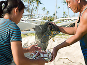 Imelda Esgana, fish vendor discussing the day's catch with a fisherman, Talisay, Santa Fe, Bantayan Island, The Philippines. Every morning at 7 am Imelda meets the fishermen as they return from the sea with their catch. After sorting and weighing,  Imelda sells the fish locally by going house to house. On November 6 2013 Typhoon Haiyan hit the Philippines and was one of the most powerful storms to ever make landfall.  Three-quarters of the island's population of about 136,000 depend on fishing as their main source of income. Thousands lost their boats and equipment in the storm. Oxfam is working to support the immediate and long-term needs of affected communities on Bantayan Island including establishing boat repair stations.