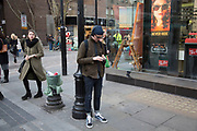 Stylish man checking his smartphone on a street corner in Covent Garden, London, UK. Wearing turn up skinny jeans and trainers.