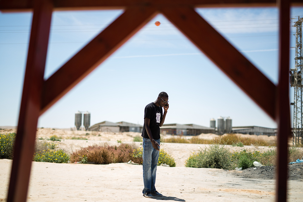 Mutasim Ali, an African asylum seeker from Sudan is seen talking on his mobile phone outside Holot detention center, where African migrants are being held, in the Negev Desert, southern Israel, on May 4, 2015.