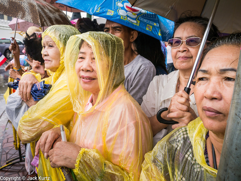 """05 MAY 2013 - BANGKOK, THAILAND:   Thais wait in the rain to see Bhumibol Adulyadej, the King of Thailand, Sunday. The King and Queen, who are both hospitalized and in poor health, did not attend Sunday's event. May 5 marks the 63rd anniversary of the Coronation of His Majesty King Bhumibol Adulyadej. The day is celebrated as a national holiday; since this year it falls on a Sunday, the holiday will be observed on Monday May 6, and as such all government offices and commercial banks will close for the day. HM King Bhumibol Adulyadej is the longest reigning monarch in the world. Each year on the 5th of May, the Kingdom of Thailand commemorates the day when, in 1950, the Coronation Ceremony was held for His Majesty King Bhumibol Adulyadej, the 9th in the Chakri Dynasty (Rama IX). On the 5th of May, His Majesty conducts a merit making ceremony, presenting offerings to Buddhist monks, and leads a """"Wien Thien"""" ceremony, walking three times around sacred grounds at the Temple of the Emerald Buddha.    PHOTO BY JACK KURTZ"""
