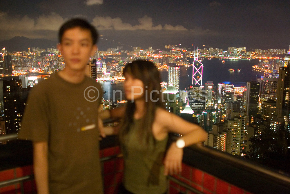Two Chinese tourists pose to have their photograph taken from the Victoria Peak viewing platform. As night falls from this classic viewpoint the entire view across Hong Kong Harbour can be seen. The view sweeping down through Mid-levels to Central, along to Causeway Bay, all the way along Hong Kong Island's coast across North Point, Quarry Bay to Wan Chai. Also over the water we see the Chinese mainland area Kowloon.