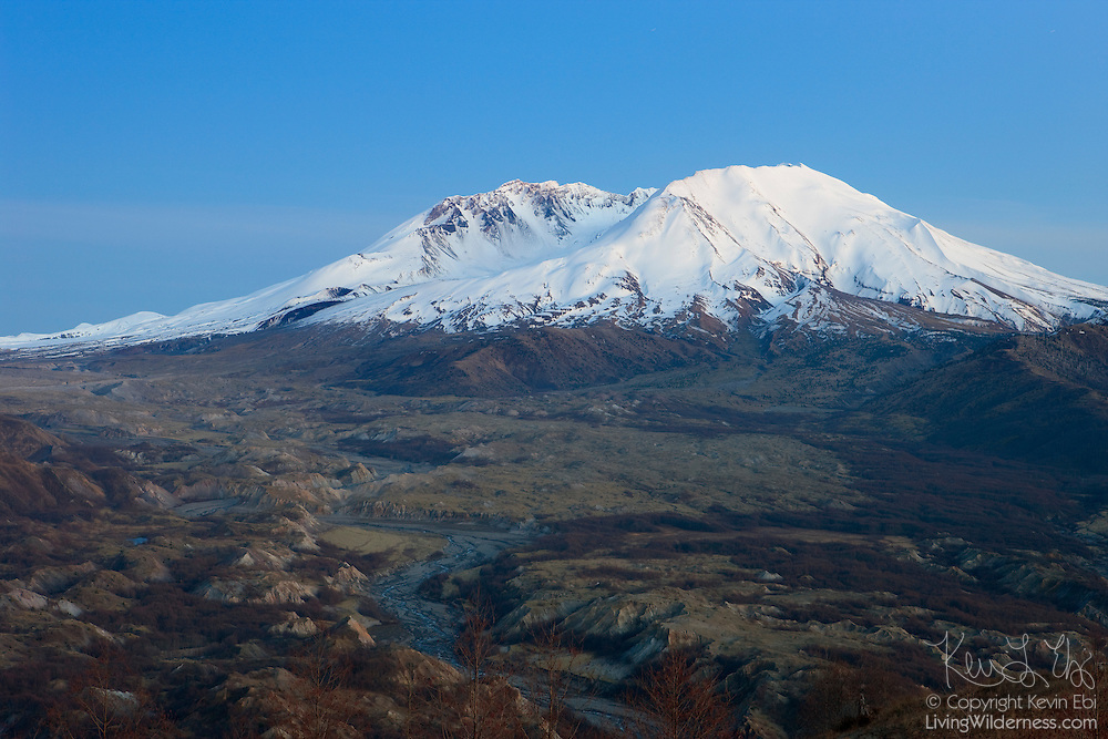 Mount St. Helens glows bright white in the alpenglow after sunset. The Toutle River winds through the blast zone created during the May 18, 1980 eruption. That eruption reduced the Washington mountain's summit from9,677 feet (2,950 m) to 8,365 feet (2,550 m).