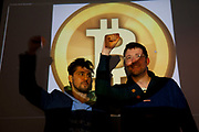 WATERLOO, LONDON, UK - APRIL 1, 2013. Amir Taaki and Jonathan James Harrison with a projection of the Bitcoin logo. Interior of a second squat where subjects working with Bitcoin operate and live. This squat is also where Occupy London activists are based. (Photo by Mike Kemp / For The Washington Post.)