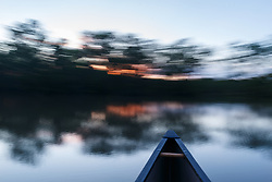 Canoe and sunset on water near Big Spring after Trinity River flood, Great Trinity Forest, Dallas, Texas, USA